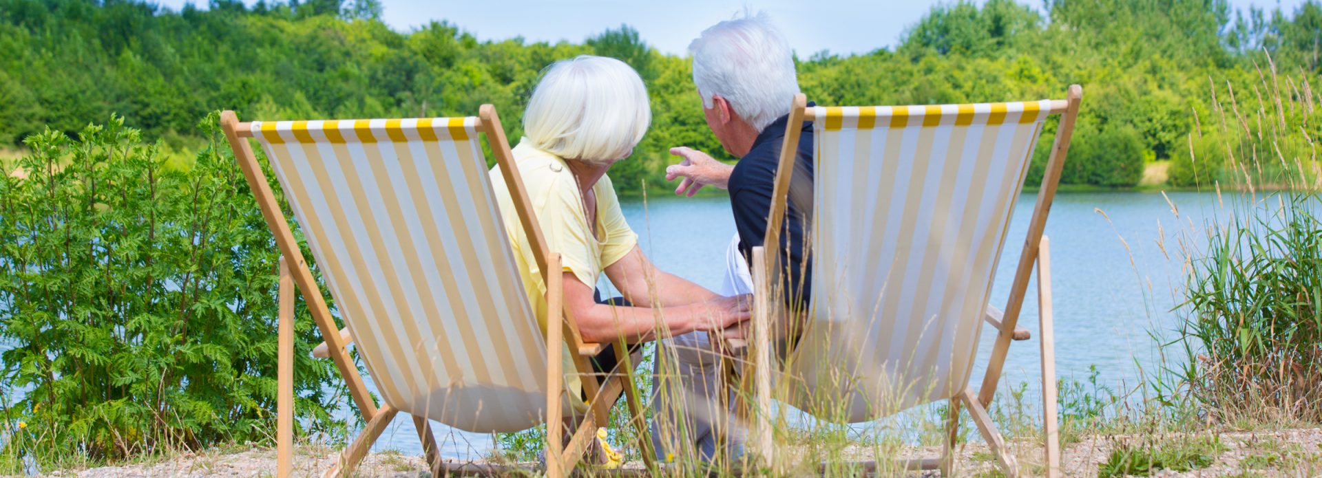 Retired couple sat by lake on deckchairs. Viewed from the back.