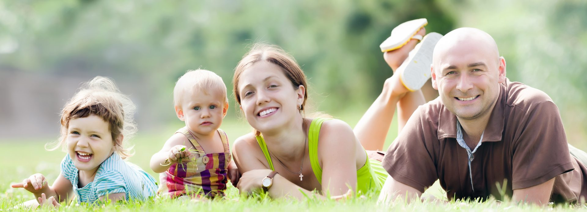 Happy family of four enjoying time at grass in summer park