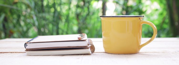 Notebook and yellow mug on table