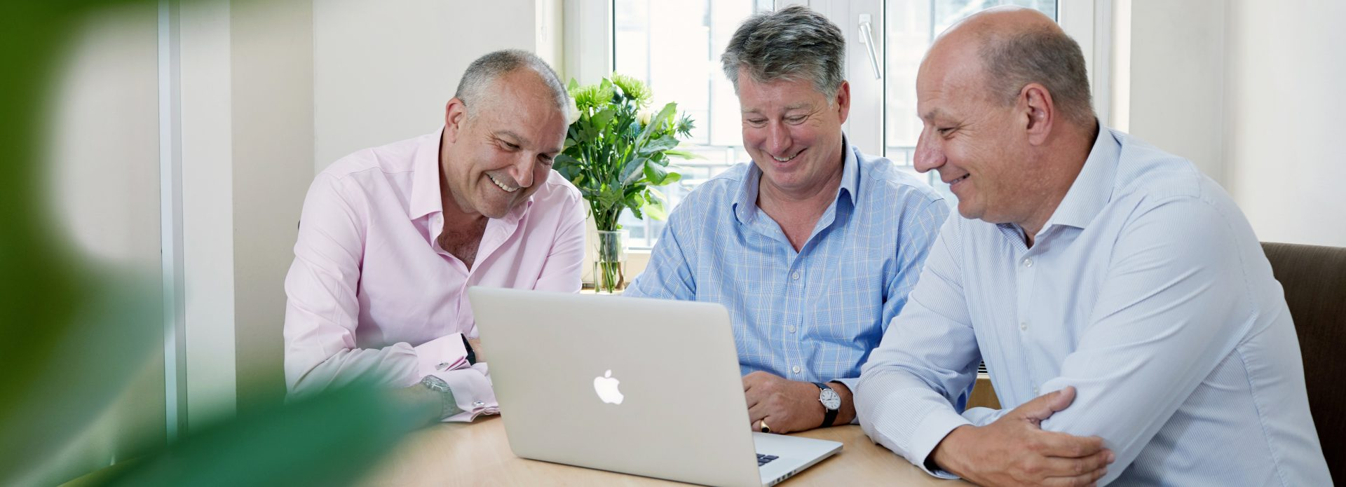 3 business men looking at laptop