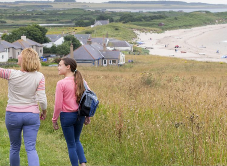 Family walking along cliff top.